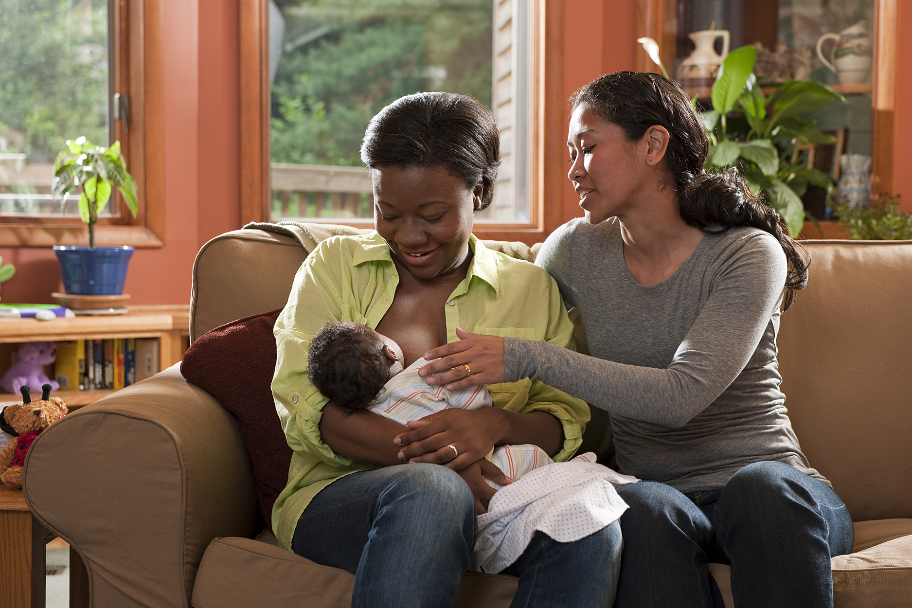 Breastfeeding counselor helping new mother breastfeed